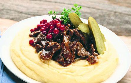 Guiso tradicional de reno con puré de patatas, pepinillos y arándanos