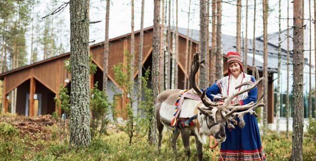 Mujer Sami y reno en el bosque que rodea al hotel Nova Skyland