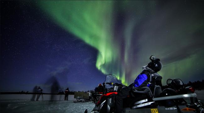Disfrutando de la visión de la Aurora Boreal durante un safari con moto de nieve en Saariselkä
