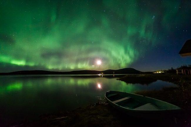 La Aurora Boreal y la Luna reflejadas en las frías aguas de un lago durante el otoño