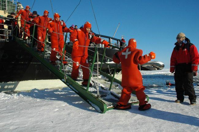 Vestidos con trajes estancos dispuestos a bañarse en las frías aguas del mar Bàltico