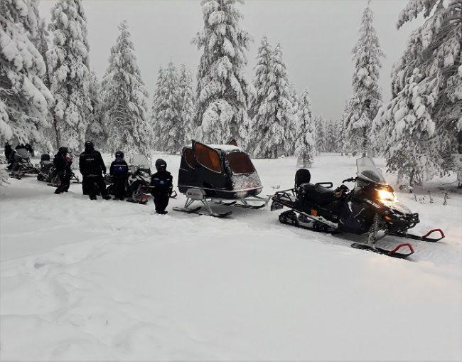 Safari con motos de nieve eléctricas. Los niños van en el trineo cubierto