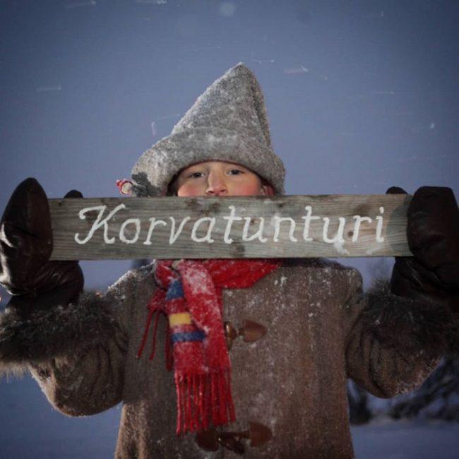 Un pequeño elfo sosteniendo un cartel de Korvatunturi