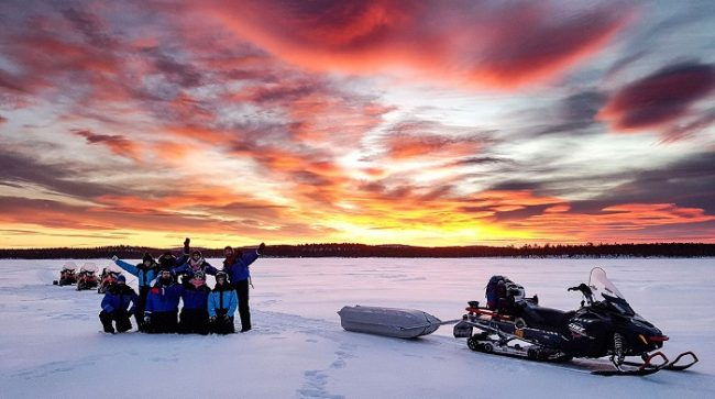 Bonito amanecer durante una excursión con moto de nieve en el lago Inari
