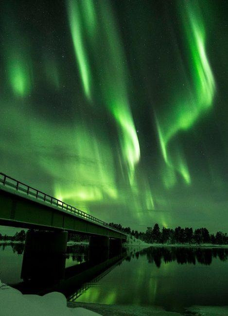 El puente sobre el río Paatsjoki en Nellim con la Aurora Boreal