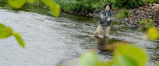 Mujer pescando en uno de los numerosos ríos que hay alrededor de la ciudad de Kuusamo