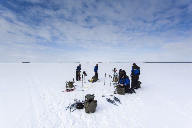 Grupo de turistas preparandose para pescar en el hielo en Laponia