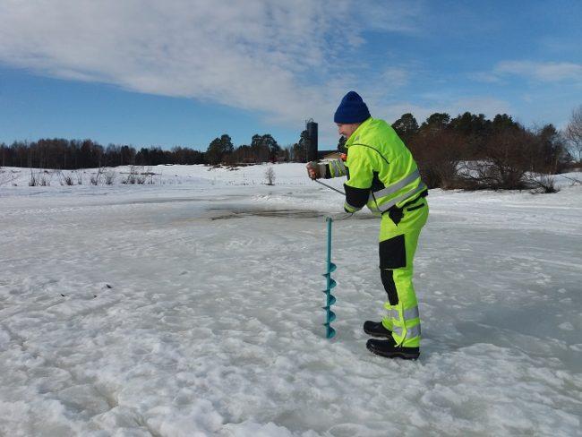 Pescador haciendo un agujero en el hielo con la barrena manual