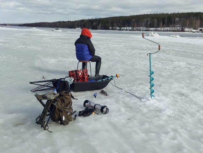 Pescando en un río helado. Se puede observar, entre otras cosas, la barrena de hielo y la mochila-silla