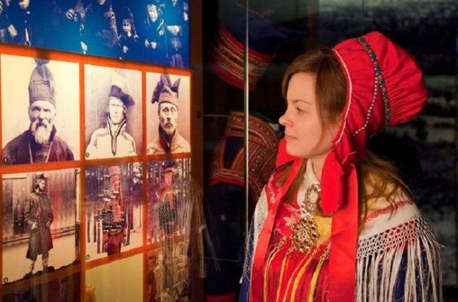 Mujer Sami mirando fotos antiguas de gente Sami