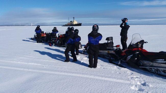 Excursión con moto de nieve en el mar Báltico. Al fondo el rompehielos Sampo