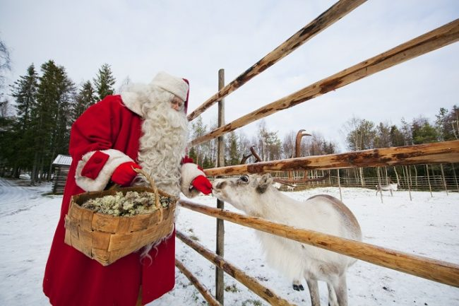 Papá Noel alimentando a un pequeño reno
